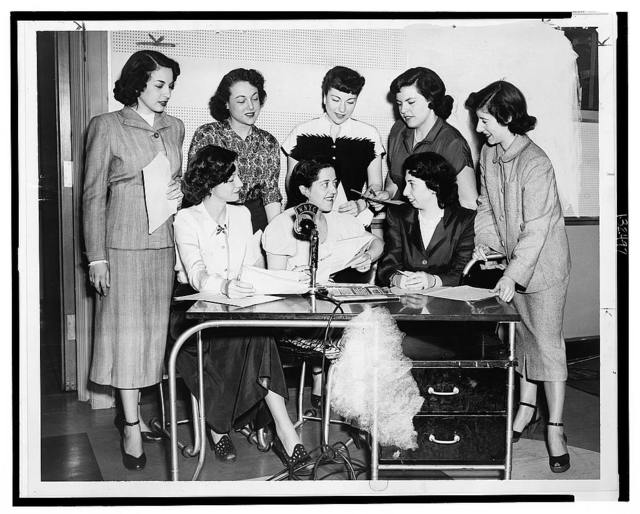 [Gathered behind desk and microphone celebrating radio station WNYC's 25th anniversary are (l to r) standing: Miriam Cutler, Dulcie Rogers, Marilyn Tack, Patti Bolton, Lynn Thiras and seated: Anita Paige, Lillian Blake, and Rita Ostrow] / World Telegram photo by F. Palumbo.