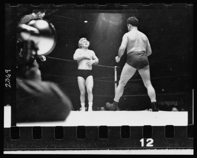 [A wrestler strides toward Gorgeous George who stands near a corner of the ring with his hands on his chest where he had received a blow in the previous maneuver in the wrestling match]