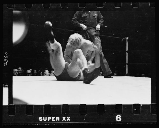 [Gorgeous George attempting to pin to the mat another wrestler during a wrestling match]