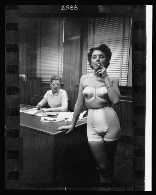 [Lingerie model, wearing a girdle and strapless bra, smoking in an office; in the background a woman sits at a desk] / Stanley Kubrick.