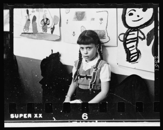 [Young girl, half-length portrait, standing against wall displaying art work, in classroom in Chicago, Illinois]