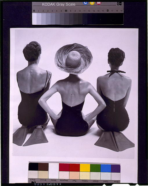 [Back view of fashion models in swim suits, two kneeling wearing swim fins, and one seated]