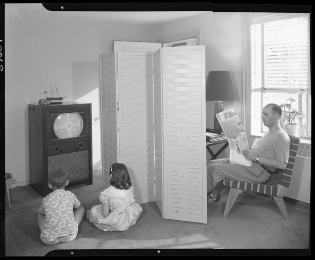 Hilda Kassell, E. 53rd St., New York City. Father reading newspaper, two children viewing television