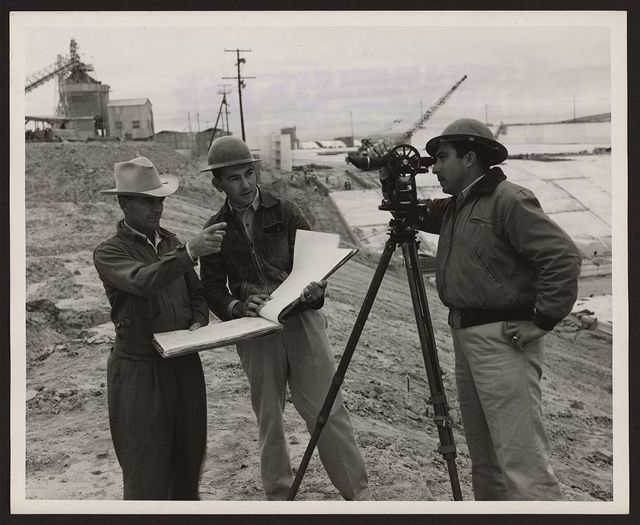 [Engineers R.D. Collons, of the United States (left), Antonio Benavides (center) and Enrique Medina looking through transit-level, of Mexico, confer at the spillway on the United States side of the joint U.S.-Mexico Falcon Dam construction project on the Rio Grande River]