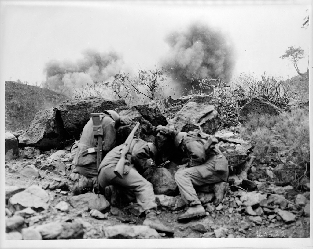 Korean Conflict. Men of the 3rd Battalion, 34th Infantry Regiment, 35th Infantry Division, covering up behind rocks to shield themselves from exploding mortar shells, near the Hantan River in central Korea