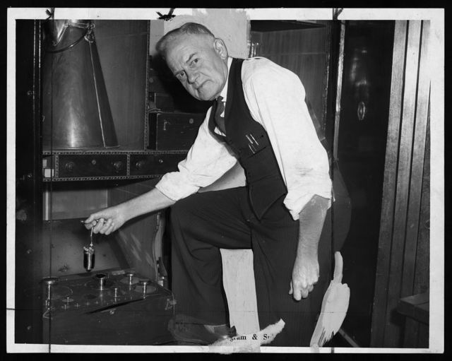 [Matthew A. Donohue, inspector of weights and measures for the N. Y. Department of Markets holding a weight used to check scales for accuracy] / World Telegram & Sun photo by Dick De Marsico.