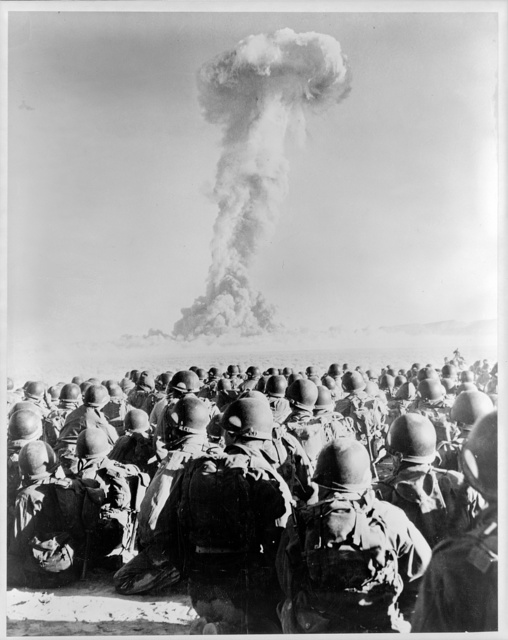 [Nevada - Frenchman's Flat - members of 11th AB Div. kneel on ground as they watch mushroom cloud of atomic bomb test]