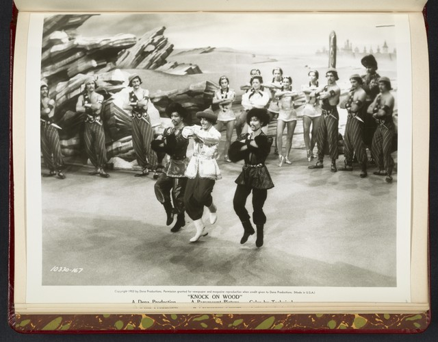 "[ Danny Kaye dancing onstage with male characters in ethnic costume - scene from ""Knock on Wood""]"