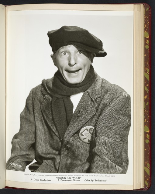 "[ Danny Kaye in winter clothes with scarf and cap makes silly face - scene from ""Knock on Wood""]"