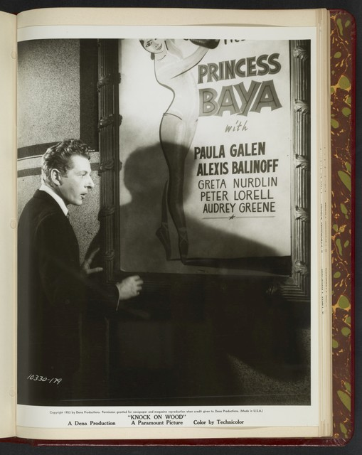 "[ Danny Kaye standing outside next to a theatre poster - scene from ""Knock on Wood""]"