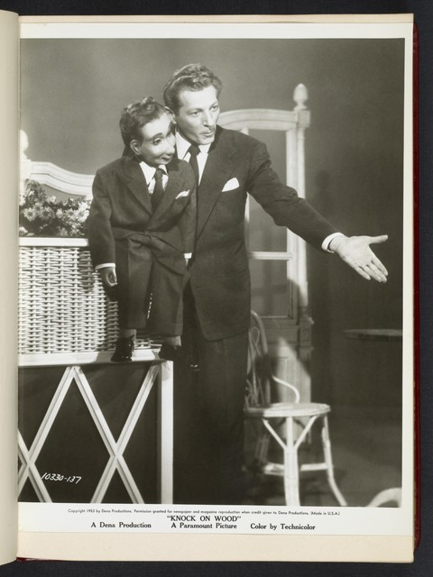 "[ Danny Kaye with ventriloquist doll gesturing to audience - scene from ""Knock on Wood""]"