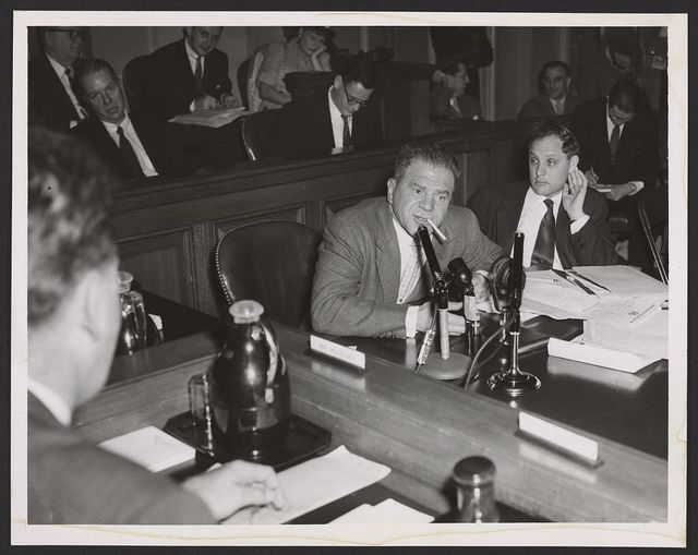 [Lionel Stander, with cigarette hanging from his lips, testifying before the House Un-American Activities Committee; attorney Leonard Boudin is sitting next to him] / World-Telegram photo by Walter Albertin.