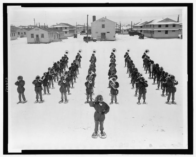 [ The 82nd Airborne Division band, under direction of Cpl. Charles Wood, playing reville during the Army's winter training exercise at Fr. Drum, New York]