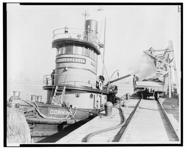 [Ashes from the stokehold of a tugboat are blown into a railroad freight car at dockside] / World Telegram & Sun photo by Roger Higgins.