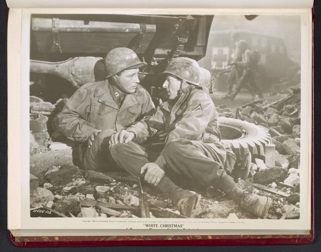 "[ Bing Crosby and Danny Kaye crouching behind a military jeep - scene from ""White Christmas""]"