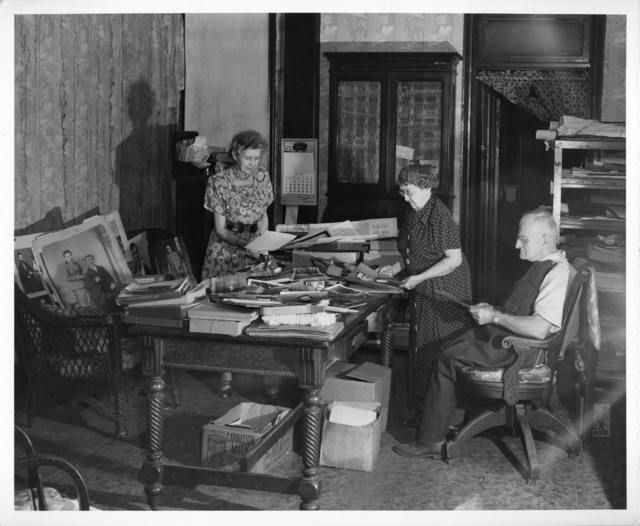 [Interior of L.C. Handy Studio, 494 Maryland Ave., SW, Washington, D.C., with Handy's daughters, Mrs. Mary Evans and Mrs. Alice Cox, and Mr. Edgar Cox (left to right) looking at prints dating back to Mathew Brady piled on table] / photograph by the Library of Congress.