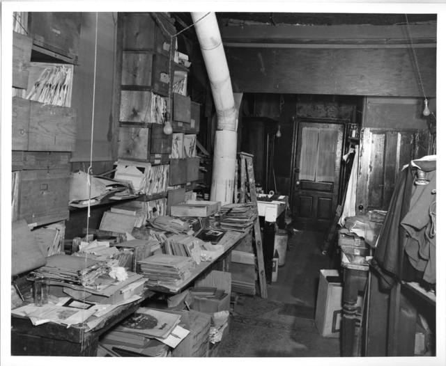 [Interior of L.C. Handy Studio, 494 Maryland Ave., SW, Washington, D.C., with piles of glass negatives dating back to Mathew Brady on the left and camera under cloth on the right] / photograph by the Library of Congress.