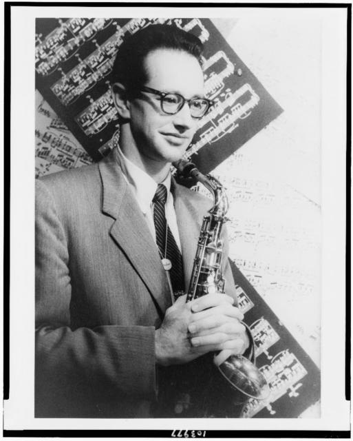 [Portrait of Paul Desmond holding saxophone with backdrop of sheet music]