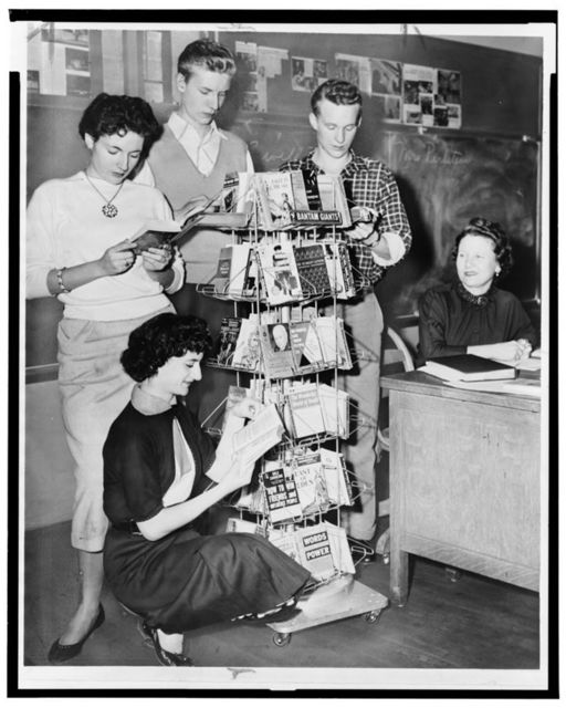 [Connie Masi, Sheila Macy (kneeling), Ernest Sims, and Fred Kimtscher students at William Cullen Bryant High School gather around mobile shelving in the library] / World Telegram & Sun photo by Herman Hiller.