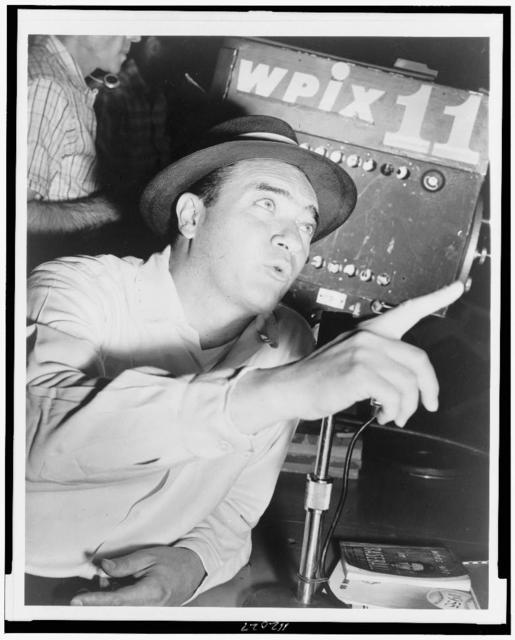 [Mel Allen, half-length portrait, at microphone, facing right, looking and pointing upward] / World Telegram & Sun photo by Al. Ravenna.