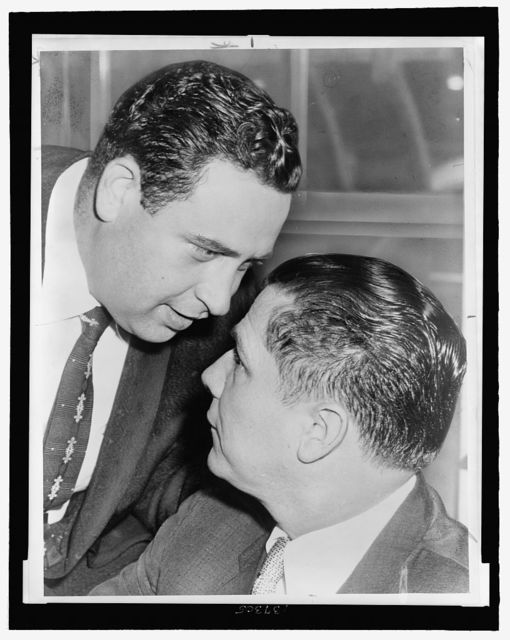 Bernard Spindel whispers in ear of James R. Hoffa after court session in which they pleaded innocent to illegal wiretap charges / World Telegram & Sun photo byRoger Higgins.