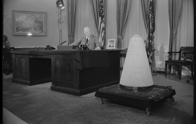 [President Dwight Eisenhower giving a television speech in the White House about science and national security, next to a nose cone of an experimental missile which had been into space and back]