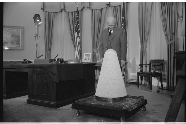 [President Dwight Eisenhower looking at a nose cone of an experimental missile which had been into space and back, during a television speech in the White House about science and national security]