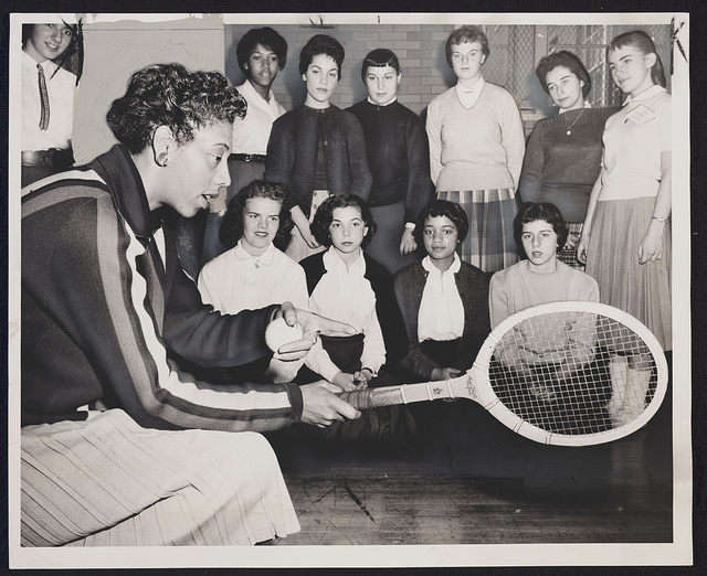 Tennis talk Althea Gibson, U.S. and Wimbledon tennis champion, gives some pointers on the game which has brought her international fame. Some 500 students attended the tennis clinic yesterday at Midwood HS, directed by Murray Eisenstadt, varsity coach / / World Telegram & Sun photo by Ed. Ford.