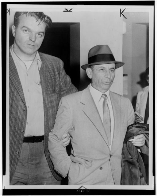[Meyer Lansky, half-length portrait, facing slightly right, being led by detective for booking on vagrancy charge at 54th Street police station, New York City] / N.Y. World Telegram & Sun photo by Orlando Fernandez.