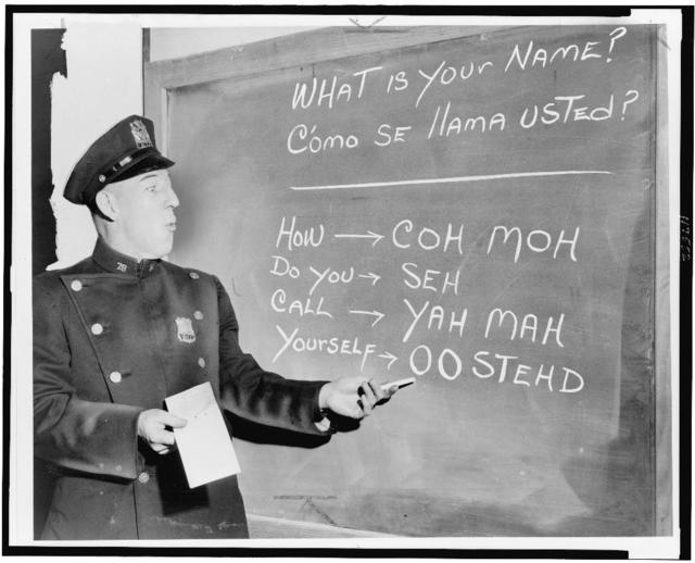 [Officer Richard Perry practices basic Spanish phrases using phonetic syllables written on blackboard] / World Telegram & Sun photo by Dick DeMarsico.