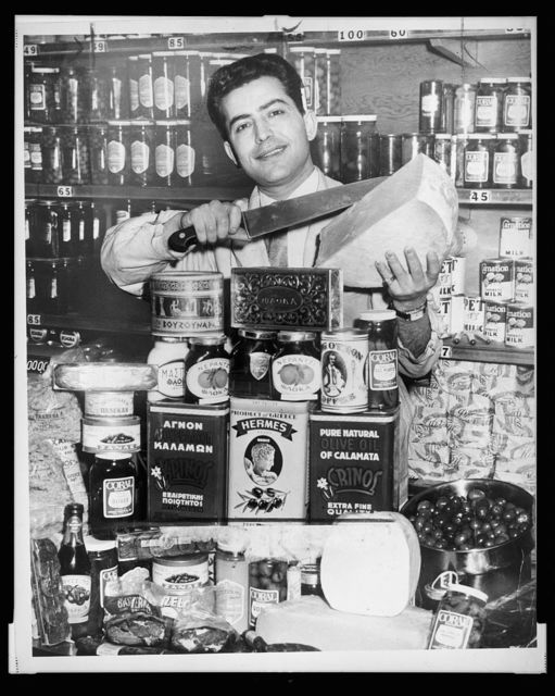 Gus Marris is shown with a large display of Greek foods at the Couphopoulos Delicatessen at 306 W. 40th St. / World Telegram & Sun photo by Fred Palumbo.