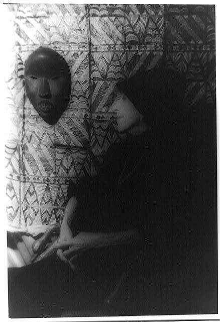 [Portrait of Isak Dinesen (Baroness Karen Blixen) looking at African mask and textile on wall]