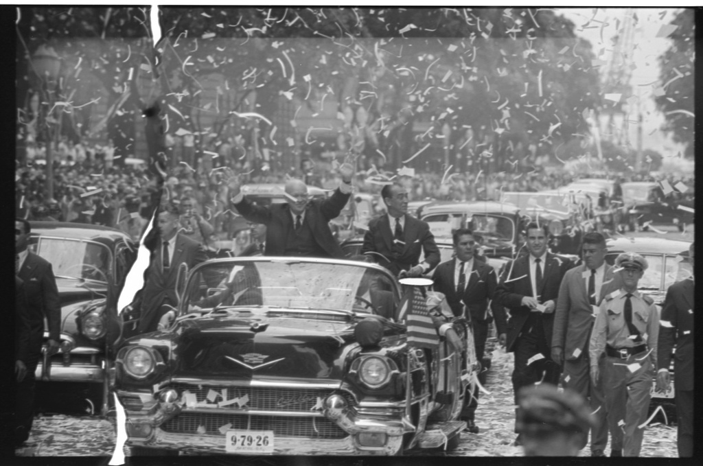 [President Dwight D. Eisenhower standing in automobile, waving to crowds during a ticker tape parade during his visit to Rio de Janeiro, Brazil]