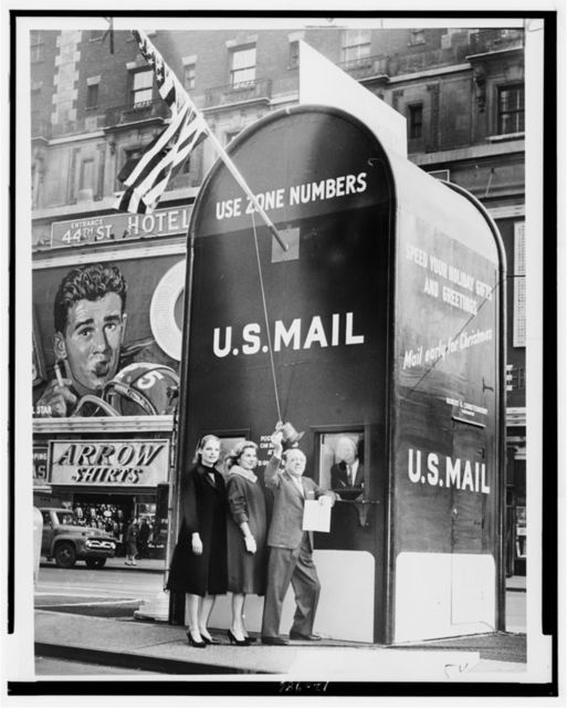 [Actresses Millette Alexander and Louise King, and nightclub entertainer Ted Lewis, stand outside a giant mailbox stamp selling booth in Times Square, New York City, while Assistant Postmaster Aquiline F. Weierich dispenses stamps from inside booth] / World Telegram & Sun photo by Phyllis Twachtman.