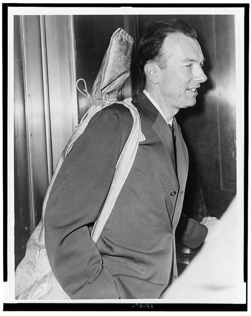 Pete Seeger arrives at Fed. Court with his guitar over his shoulder / World Telegram photo by Walter Albertin.