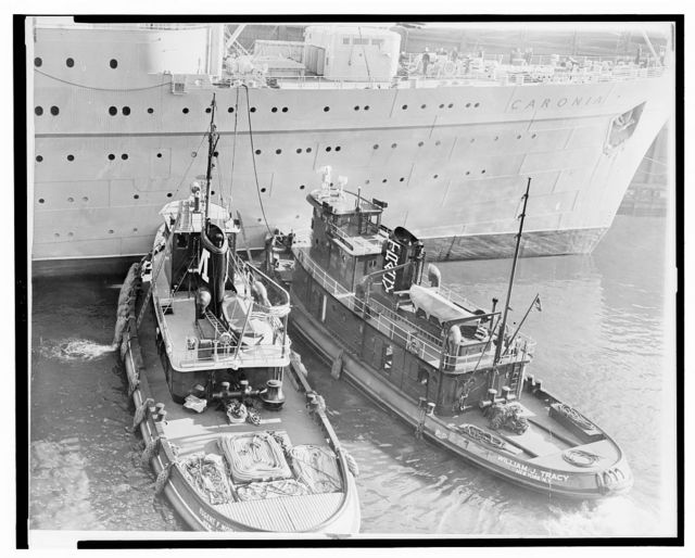 """Tug[boat]s Eugene F. Moran and William J. Tracy, two of the many """"workhorses"""" that keep New York harbor traffic moving, nudge Caronia into pier / World Telegram & Sun photo by Orlando Fernandez."""