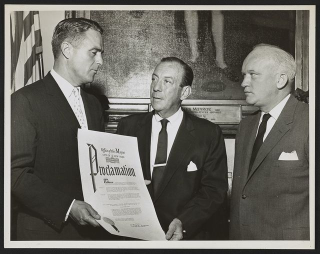 [R. Sargent Shriver holds Peace Corp Week proclamation from Mayor Wagner at City Hall, watching is James B. Donovan, Vice President of Board of Education] / World Telegram & Sun photo by Herman Hiller.