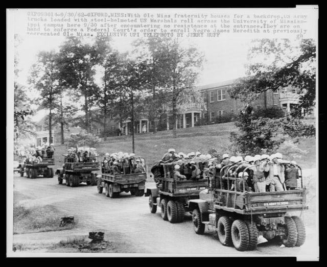 With Ole Miss fraternity houses for a backdrop, US Army trucks loaded with steel-helmeted US Marshals roll across the University of Mississippi campus / photo by Jerry Huff.