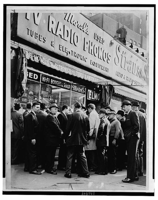 Crowd listens outside radio shop at Greenwich and Dey Sts. for news on President Kennedy / World Telegram & Sun photo by O. Fernandez.
