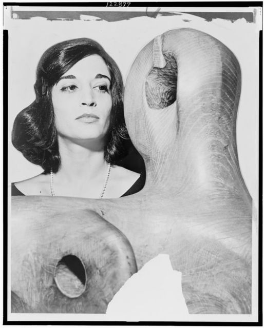 Venezuelan-born society sculptress Marisol Escobar looks quizzically at the head of a woman by British sculptor Henry Moore at new Marlborough-Gerson Gallery / World Telegram & Sun photo by Herman Hiller.