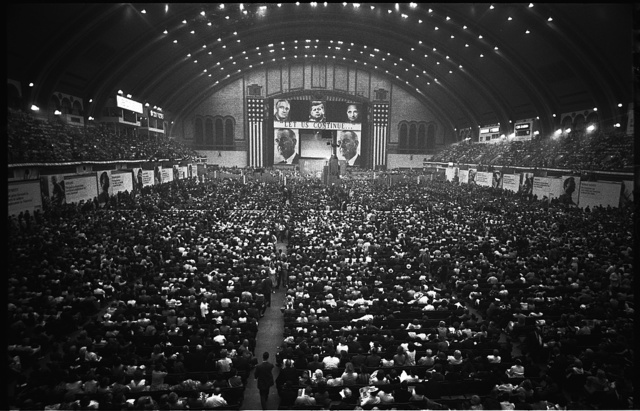 "[Aerial view of delegates and the stage with large pictures of John F. Kennedy, Harry Truman, Franklin D. Roosevelt, and Lyndon B. Johnson and the slogan ""Let us continue..."", at  the 1964 Democratic National Convention, Atlantic City, New Jersey] / WKL."
