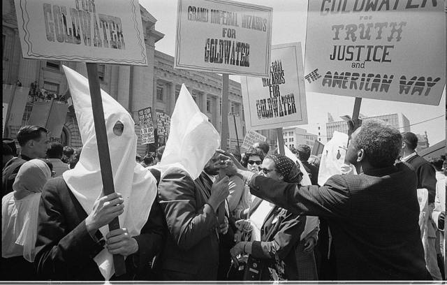 [Ku Klux Klan members supporting Barry Goldwater's campaign for the presidential nomination at the Republican National Convention, San Francisco, California, as an African American man pushes signs back] / [WKL].