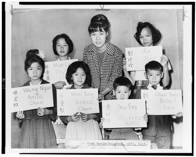 [Miss April Lou, teacher at PS 1, Manhattan, with six Chinese children, recent arrivals from Hong Kong and Formosa, who are holding up placards giving his or her Chinese name (both in ideographs and in transliteration) and the name to be entered upon the official school records] / World Telegram & Sun photo by Fred Palumbo.