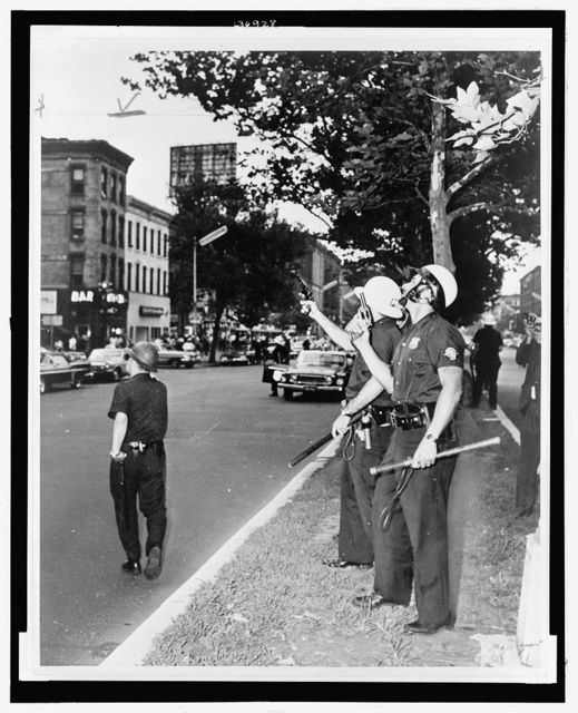[Police in Harlem standing on the street with guns drawn and pointing upwards during the July 1964 race riots] / World Telegram & Sun photo by Stanley Wolfson.