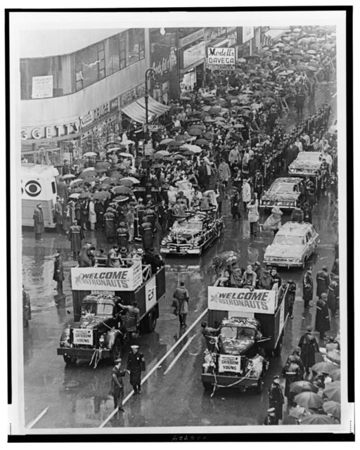 """[Aerial view of ticker tape parade for astronauts Virgil Grissom and John Young (seated in last car with Vice President Humphrey), led by trucks with signs reading """"Welcome Astronauts"""", Broadway, New York City] / World Telegram & Sun photo by Roger Higgins."""