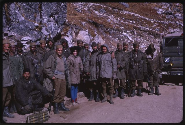 [Alice Kandell posing with guards at the Nathu La Pass, Sikkim]