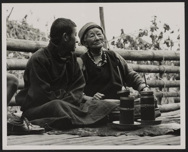 Bhutia couple drinking millet beer from a straw on their house terrace in Western Sikkim