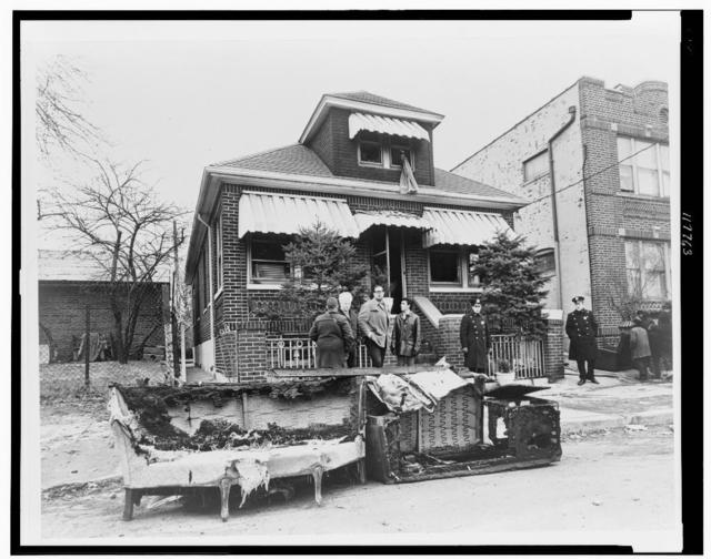 [Exterior view of home of Malcolm X, in foreground remains of charred furniture] / World Telegram & Sun photo by Stanley Wolfson.