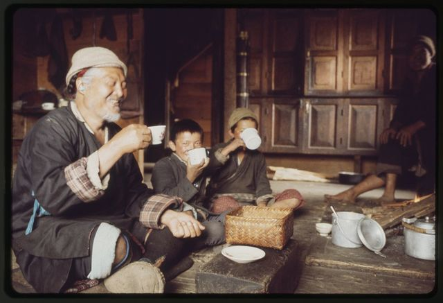 [Headman of village, Pipon, seated in house with children, drinking out of cup, Lachung, Sikkim]