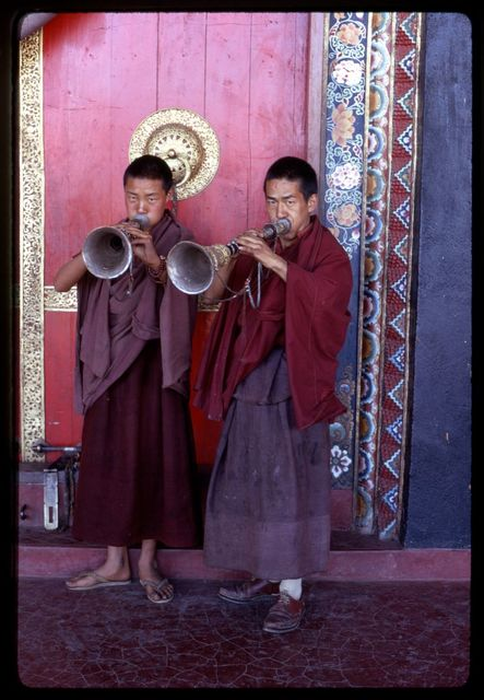 Lamas play horns at temple door, Sikkim